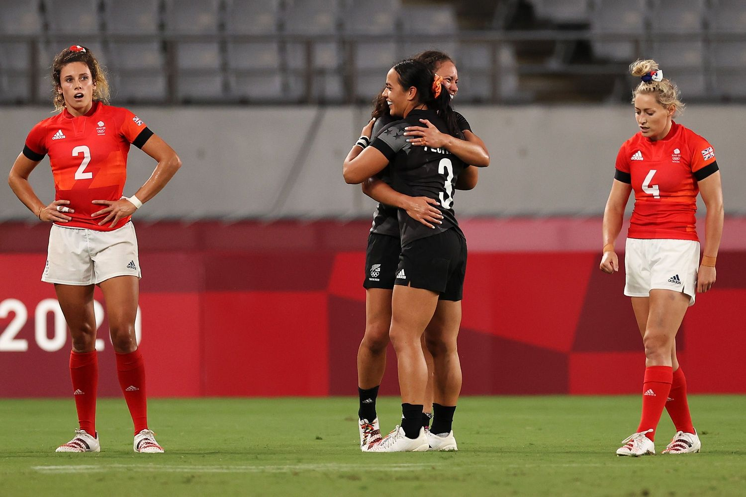 Photo of New Zealand's Ruby Tui and Stacey Fluhler celebrating as Abbie Brown and Natasha Hunt of Team Great Britain look dejected after defeat during the Rugby Sevens on day six of the Tokyo Olympics