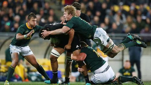 GETTING A GRIP: Pieter-Steph du Toit dives on to the back of an All Black